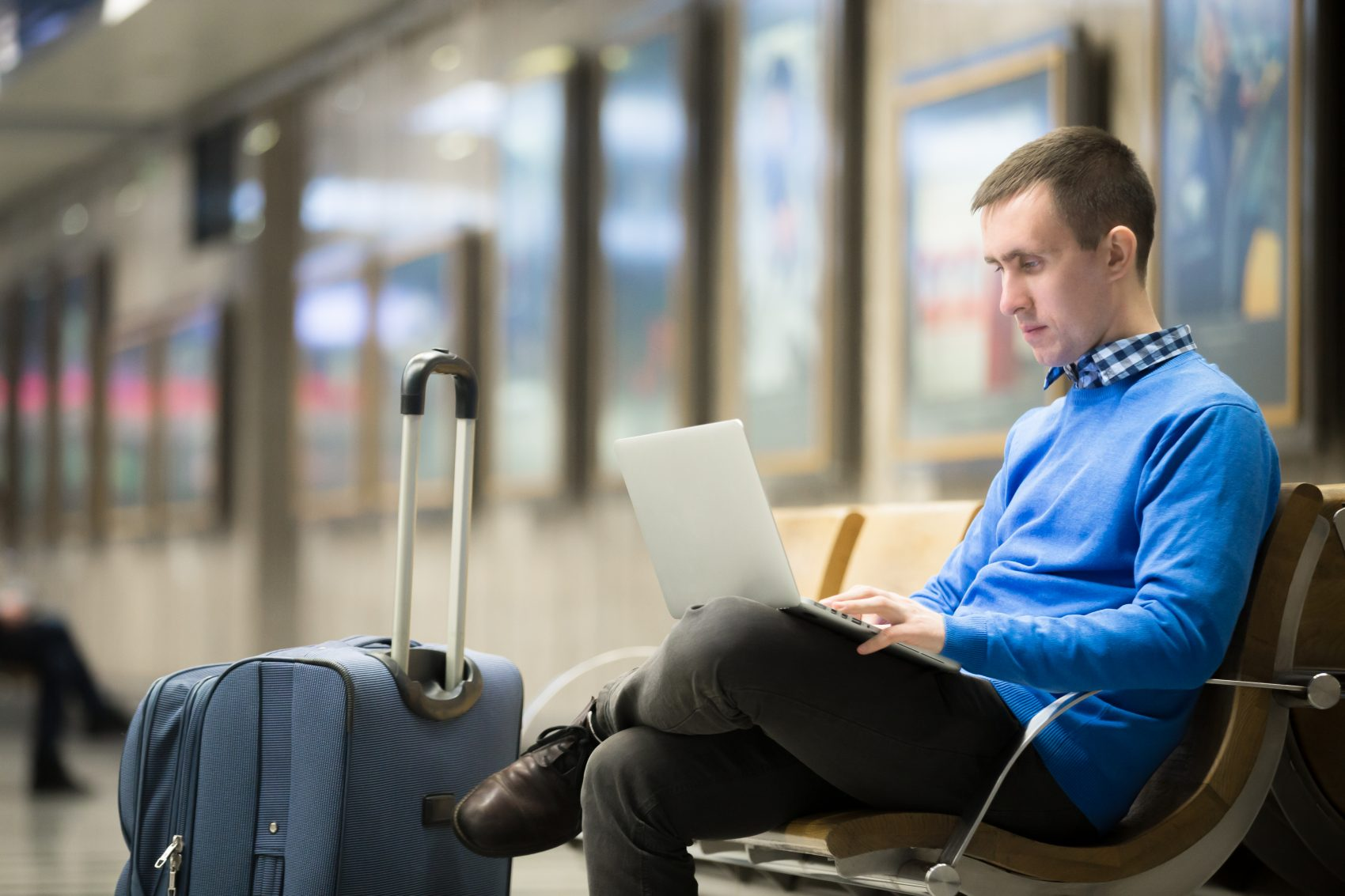 Man sitting at airport doing work - BYOD policy