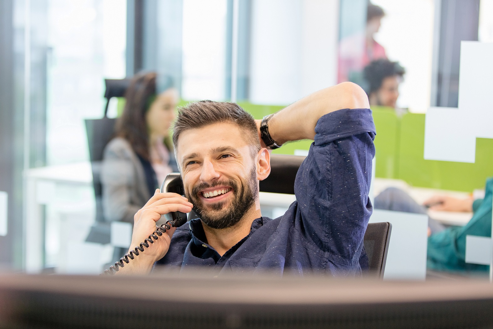 Man leaning back on chair in office while on the telephone.